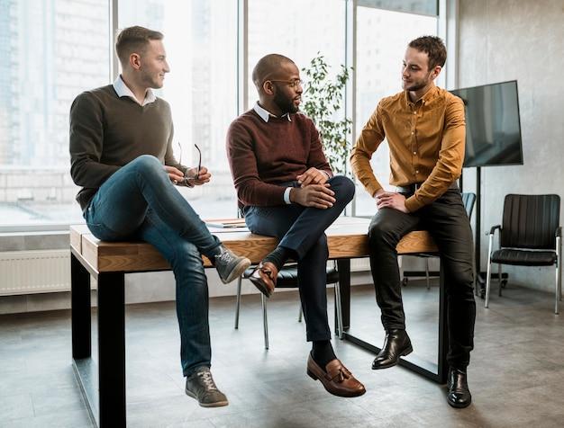 Tres hombres conversando en la oficina durante una reunión Foto gratis