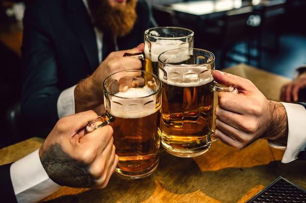 Tres hombres de traje mantienen juntas jarras de cerveza. se sientan a la mesa. Foto Premium