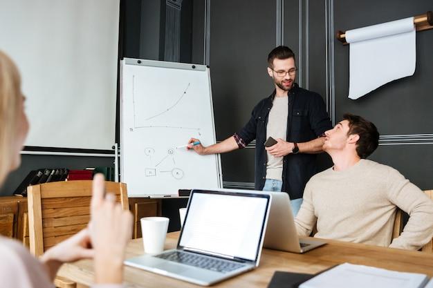 Tres jóvenes colegas sentados mientras trabajan con computadoras portátiles y escritorio Foto gratis