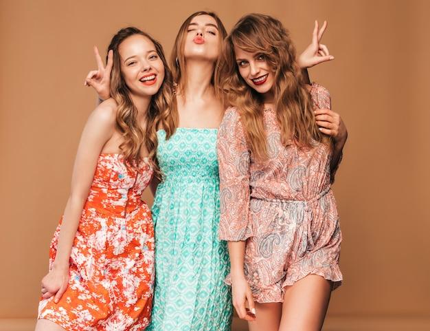 Tres jóvenes hermosas chicas sonrientes en moda casual vestidos de verano y gafas de sol. sexy mujer despreocupada posando. Foto gratis