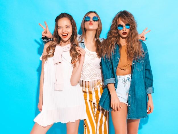 Tres jóvenes hermosas chicas sonrientes en ropa colorida moda verano. mujeres despreocupadas atractivas en las gafas de sol aisladas en azul. modelos positivos Foto gratis