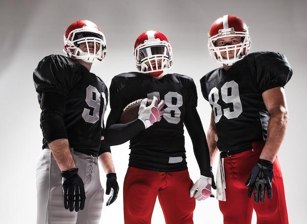 Los tres jugadores de fútbol americano posando con balón Foto gratis