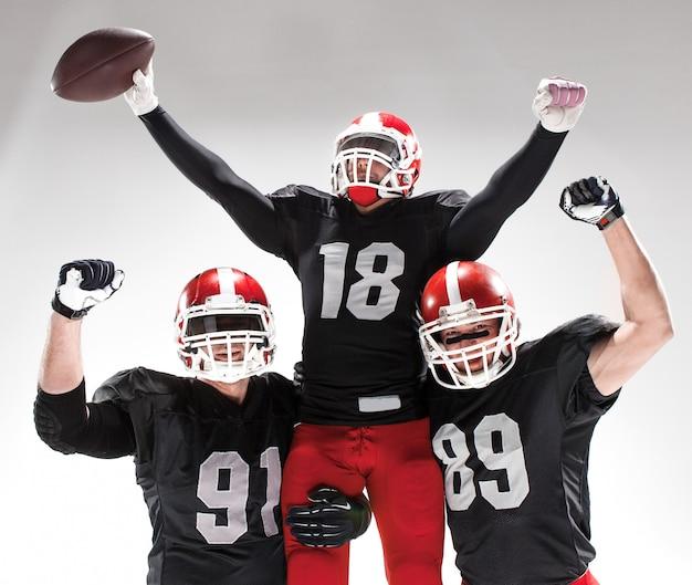Los tres jugadores de fútbol americano posando Foto gratis