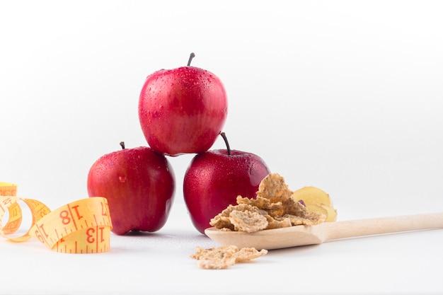 Tres manzanas con cinta métrica y cereales. Foto gratis