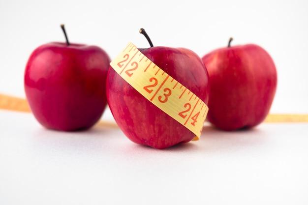 Tres manzanas con cinta métrica en la mesa Foto gratis