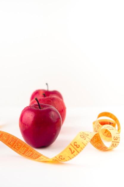 Tres manzanas rojas con cinta métrica en la mesa Foto gratis