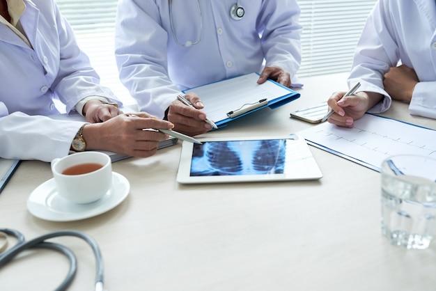 Tres médicos recortados que analizan la radiografía de tórax en el teclado digital Foto gratis