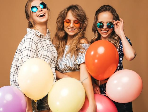 Tres mujeres hermosas sonrientes en camisa a cuadros ropa de verano y gafas de sol. chicas posando modelos con globos de colores. divirtiéndose, listo para celebrar cumpleaños Foto gratis