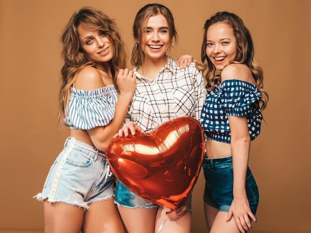 Tres mujeres hermosas sonrientes en ropa de verano camisa a cuadros. chicas posando modelos con globo en forma de corazón. listo para la celebración de san valentín Foto gratis