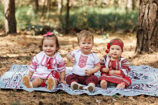Tres niños en camisas ucranianas tradicionales se sientan en tierra en bosque de la primavera. Foto gratis