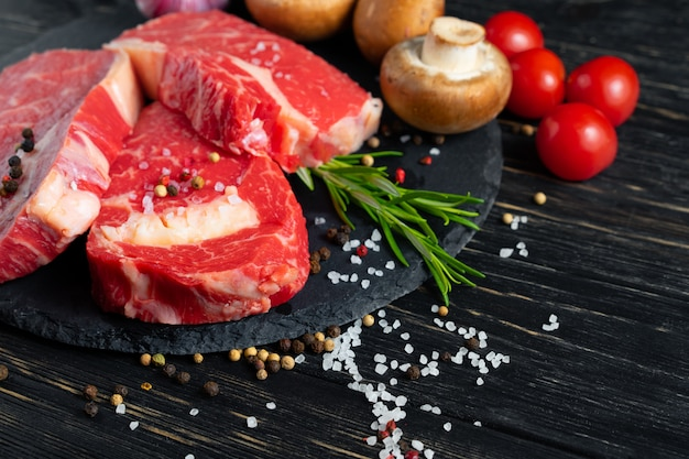 Tres piezas de jugosa carne cruda en una tabla para cortar piedra en una mesa de madera negra Foto Premium