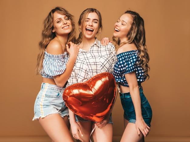 Tres sonrientes hermosas mujeres sexy en camisa a cuadros ropa de verano. chicas posando modelos con globo en forma de corazón. listo para la celebración de san valentín Foto gratis