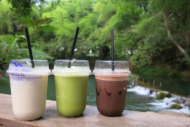 Tres vasos de bebida: cacao helado, té verde y jugo de coco frappe colocado sobre la mesa de madera en un ambiente de naturaleza fresca rodeado de árboles y un pequeño arroyo Foto Premium