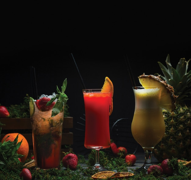 Tres vasos de cócteles de frutas tropicales. Foto gratis