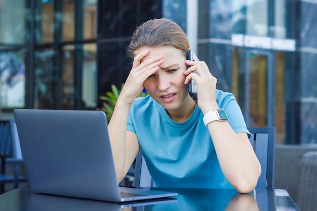 Triste molesta chica frustrada, enojada disgustada joven con laptop sentada en la cafetería con la computadora al aire libre, hablando por teléfono celular móvil inteligente. conversación negativa, llamada, malas noticias. dama desesperada Foto Premium