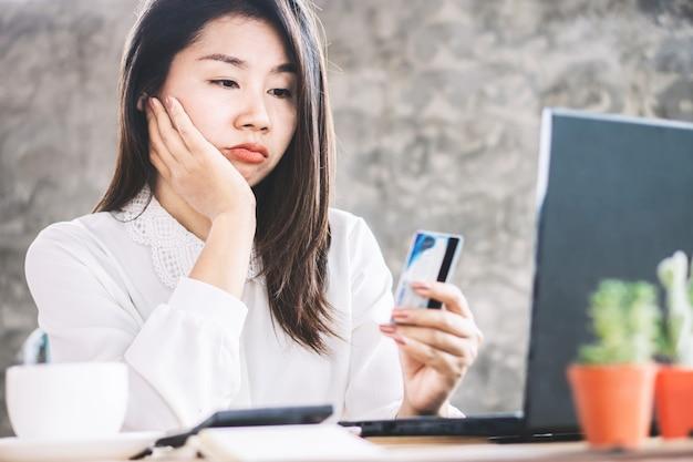 Triste mujer asiática sin dinero para tarjeta de crédito Foto Premium