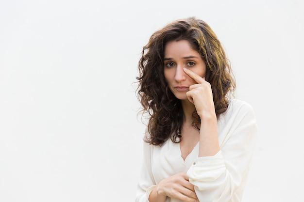 Triste mujer infeliz quitando lágrimas de la cara Foto gratis