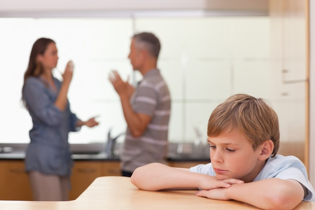 Triste niño escuchando a sus padres teniendo una discusión Foto Premium
