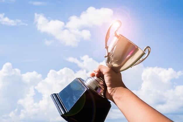 Trofeo campeón ganador colocado en la mano levantada sosteniendo Foto Premium