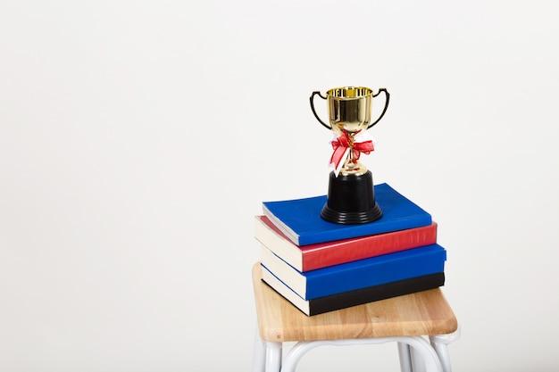 Trofeo de la taza en una pila de libros con copyspace. Foto Premium