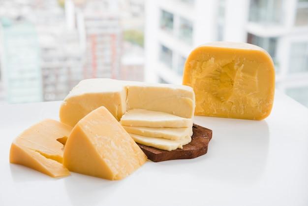 Trozo de queso cheddar y gouda en una mesa blanca cerca de la ventana Foto gratis