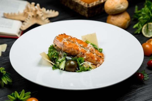Un trozo de salmón a la parrilla dentro de un plato blanco servido con vegetación y parmesano Foto gratis