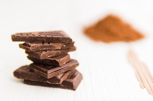 Trozos de chocolate negro y polvo de cacao borroso montón Foto gratis