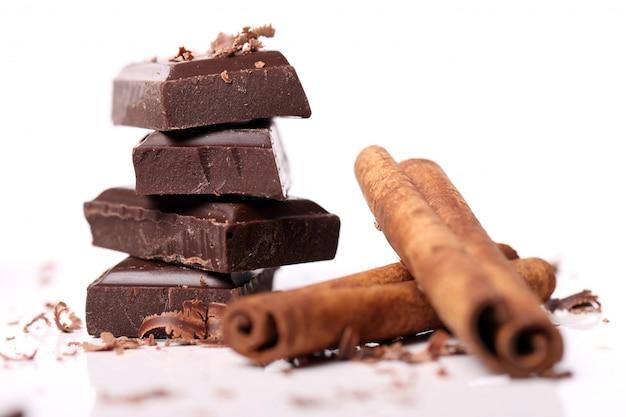 Trozos de chocolate con palitos de canela Foto gratis