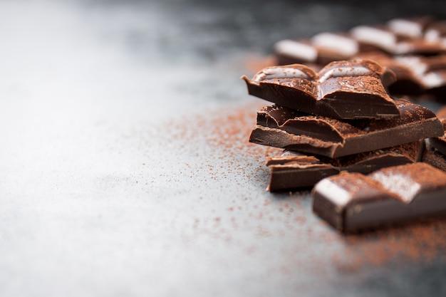 Trozos de chocolate sobre una mesa de madera y cacao espolvoreado Foto gratis