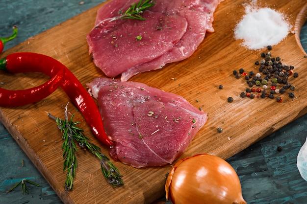 Trozos de filete de cerdo crudo con especias y hierbas romero Foto gratis