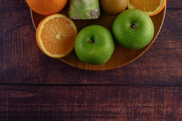 Trozos de naranja, manzana, kiwi y brócoli en un plato de madera. Foto gratis