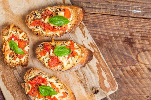 Trozos de pan con queso y tomate Foto gratis
