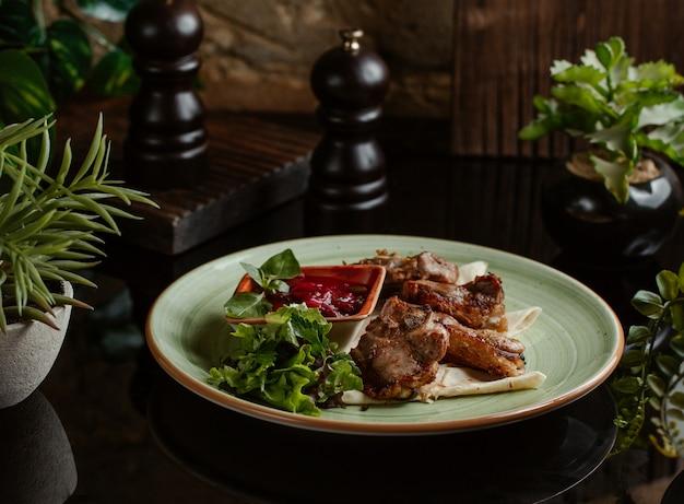 Trozos de pollo a la parrilla y presentados en un plato de cerámica amarilla. Foto gratis