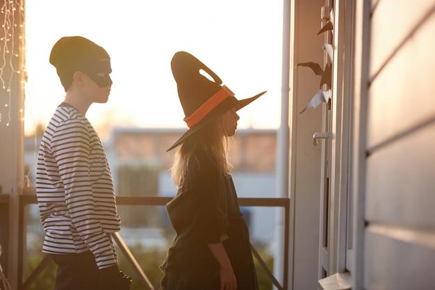Truco o trato niños esperando por la puerta en halloween Foto Premium