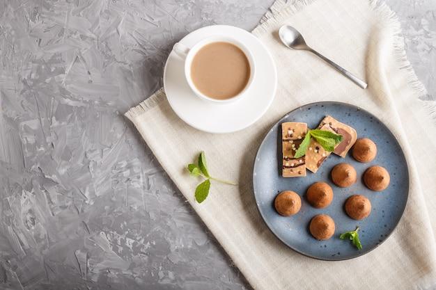 Trufa de chocolate con el pedazo de chocolate con leche en la placa de cerámica azul. Foto Premium