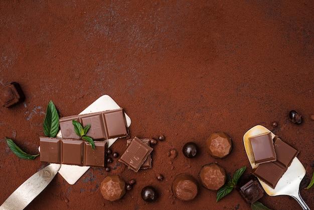Trufas de barra de chocolate y cacao en polvo con espacio de copia Foto gratis