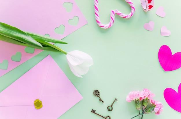 Tulipán blanco con corazones de papel en mesa Foto gratis