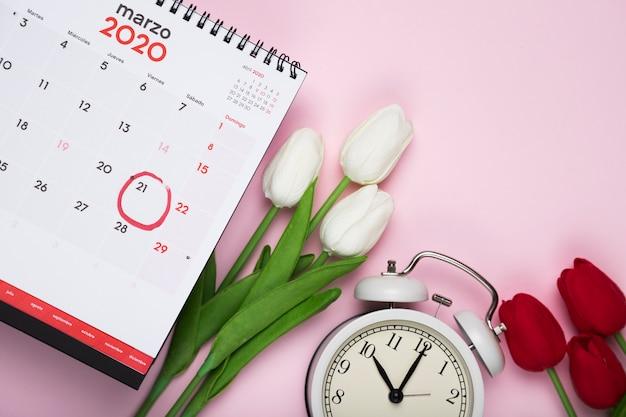 Tulipanes blancos y rojos al lado de calendario y reloj Foto gratis