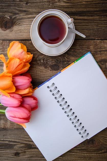 Tulipanes, cuaderno, taza de té sobre fondo de madera Foto Premium