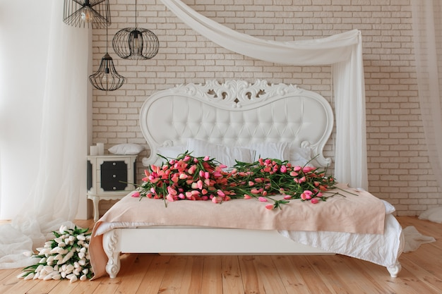 Tulipanes hermosos rojos y blancos en cama clásica grande en fondo de la pared de ladrillo Foto gratis