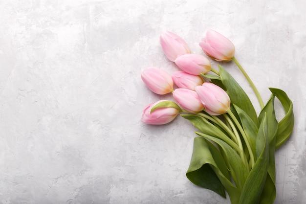 Tulipanes rosa sobre fondo de piedra gris Foto Premium
