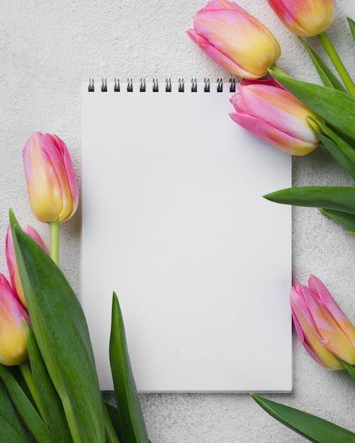 Tulipanes rosados al lado del cuaderno Foto gratis