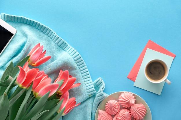 Tulipanes rosados en suéter de algodón color menta y tarjetas de felicitación Foto Premium