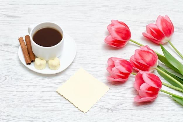 Tulipanes rosados, taza de café y canela, fondo de madera clara. Foto Premium