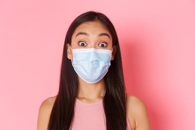 Turismo seguro, viajando durante la pandemia de coronavirus y previniendo el concepto de virus. primer plano de una turista asiática sorprendida y preguntada con máscara médica que levanta las cejas y se ve asombrada. Foto gratis
