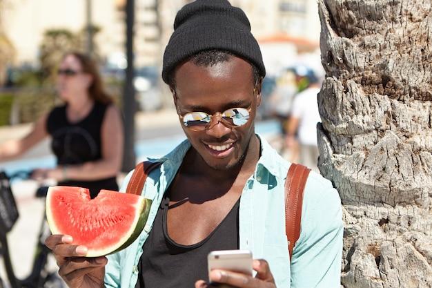 Turista afroamericano feliz comiendo sandía fresca y jugosa y usando una conexión a internet de 3g o 4g en el teléfono móvil mientras se relaja en la playa, de pie en la palmera, leyendo mensajes de amigos Foto gratis