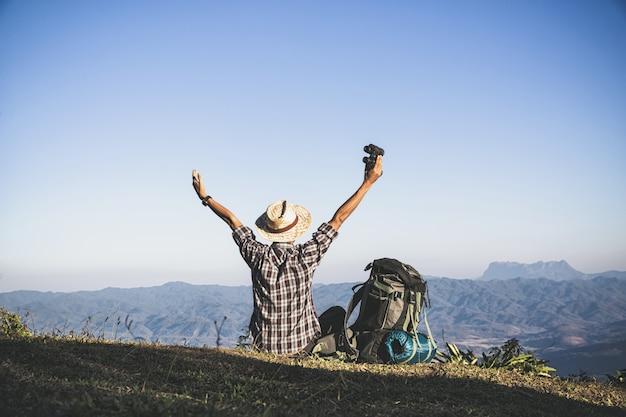 Turista desde la cima de la montaña. rayos de sol. hombre usa mochila grande contra la luz del sol Foto gratis