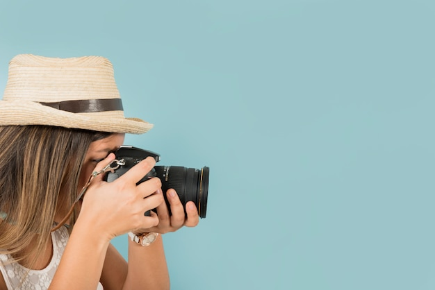 El turista femenino toma una imagen con la cámara profesional contra el fondo azul Foto gratis