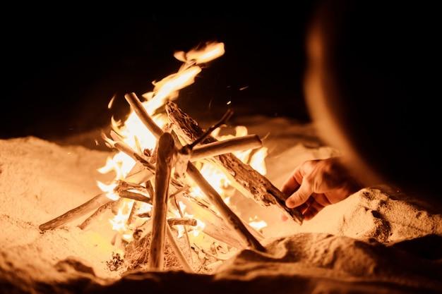 Turista hace un fuego en la playa. Foto gratis