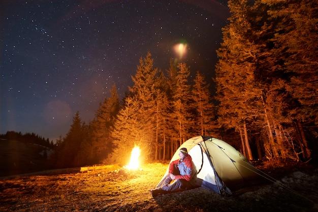 Turista masculino descansar en su campamento cerca del bosque por la noche Foto Premium